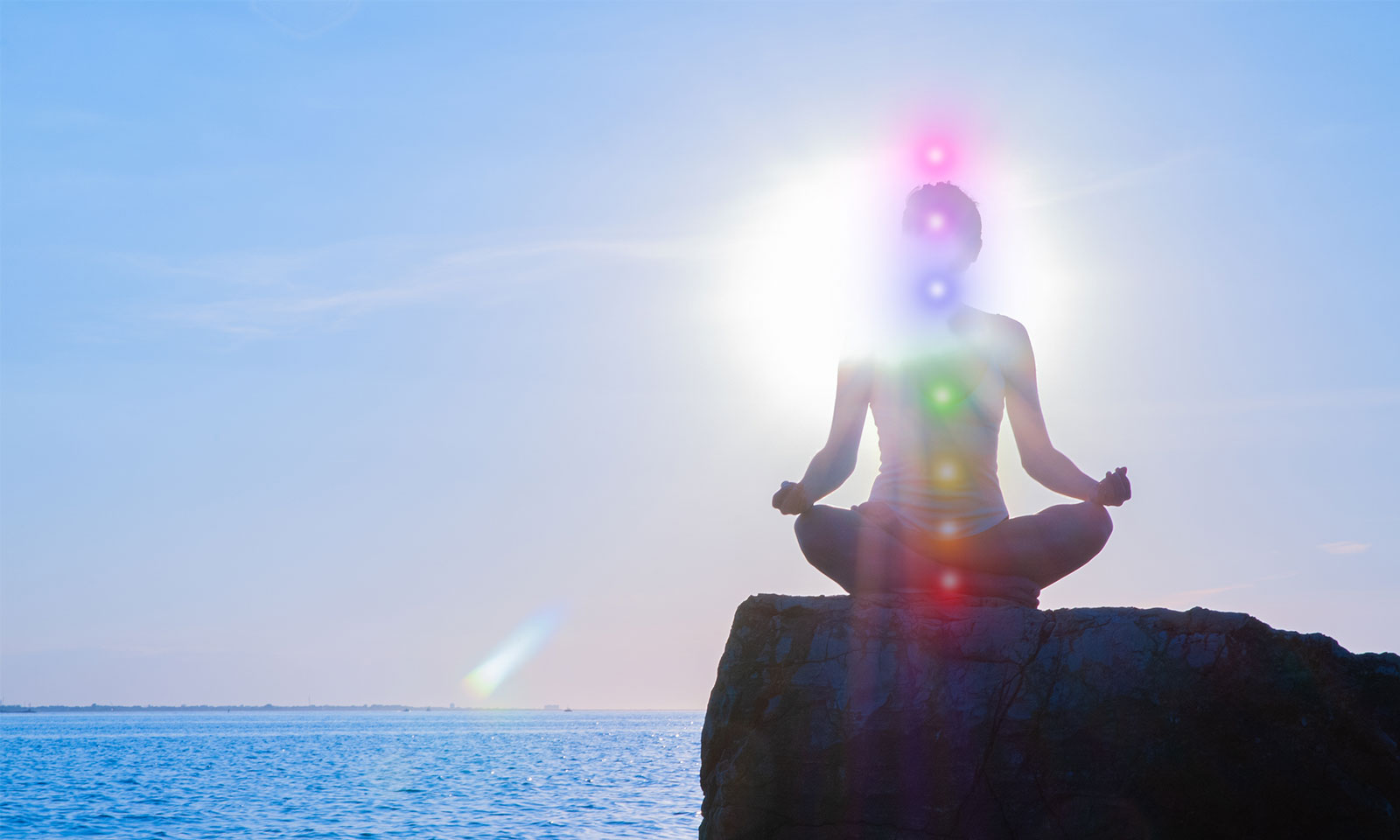 Woman sitting on a rock by the ocean in the daytime practicing kundalini yoga with her chakras glowing.