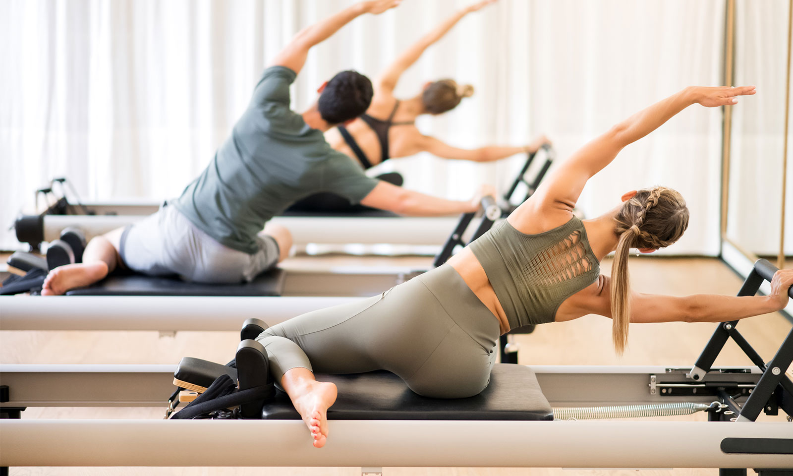 Three people exercising with their left arm up in the air on pilates exercise equipment at Institute of Awareness & Movement, Maui.