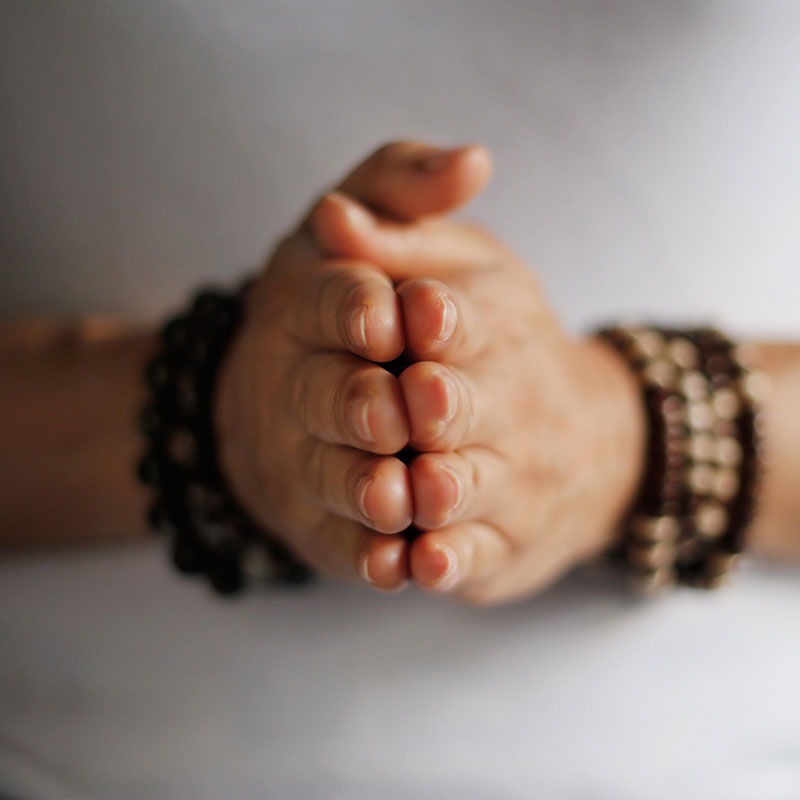 Close up of a woman's hands held in a prayer meditation position with wooden prayer beads on her wrists and a white t-shirt background.