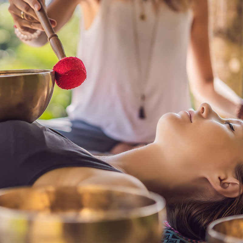 Woman lying down relaxing with a Tibetan Singing bowl healing sound session being played over her heart.